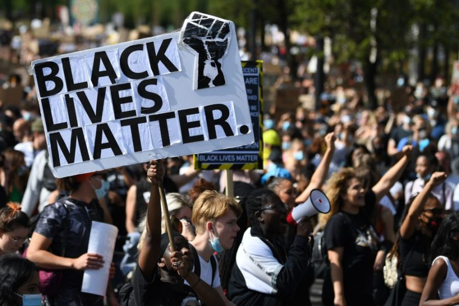 Activists%2C+some+wearing+face+coverings+or+face+masks+as+a+precautionary+measure+against+COVID-19%2C+hold+placards+as+they+attend+a+Black+Lives+Matter+march+from+Hyde+Park%2C+central+London+on+June+20%2C+2020.