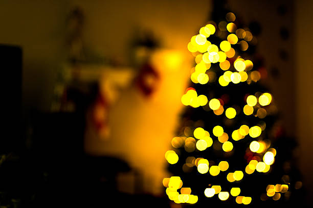 Dimly+lit+room+with+a+defocused+Christmas+tree+lit+with+lights+in+the+background.
